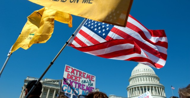 UNITED STATES – APRIL 6: Tea party activist on the East Front of the U.S. Capitol hold up signs and flags during a rally on Wednesday, April 6, 2012, days before a possible federal government shutdown. (Photo By Douglas Graham/Roll Call)
